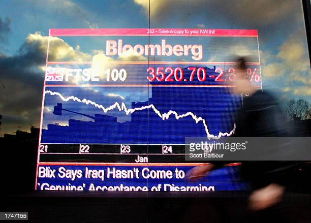 A person walks past a Bloomberg market data display January 27 2003 in London United Kingdom The FTSE 100 index fell for the eleventh straight day as...