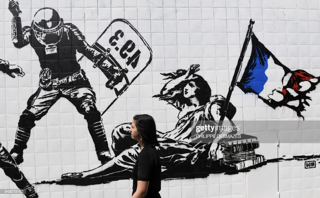 A person walks past a mural by French artist Goin on June 27, 2016 in Grenoble, southeastern France. Mayor of Grenoble Eric Piolle (EELV) Monday invoked the freedom of expression after the controversy surrounding an urban art work deemed 'anti-police,' and created as part of a festival sponsored by the municipality. / AFP / PHILIPPE