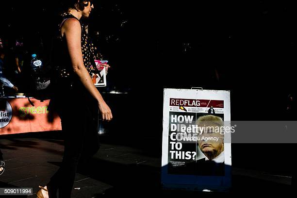 A person walks past a newspaper with Donald Trump on the cover reading 'How Did it Come to this' during a rally organised after the Australian High...