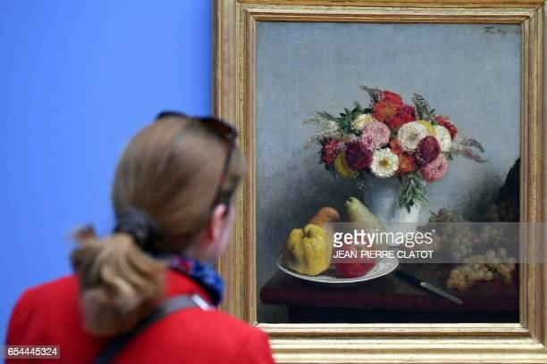 A person walks past a painting titled ' Fleurs et fruits' painted in 1860 by French painter Henri FantinLatour and displayed during the retrospective...