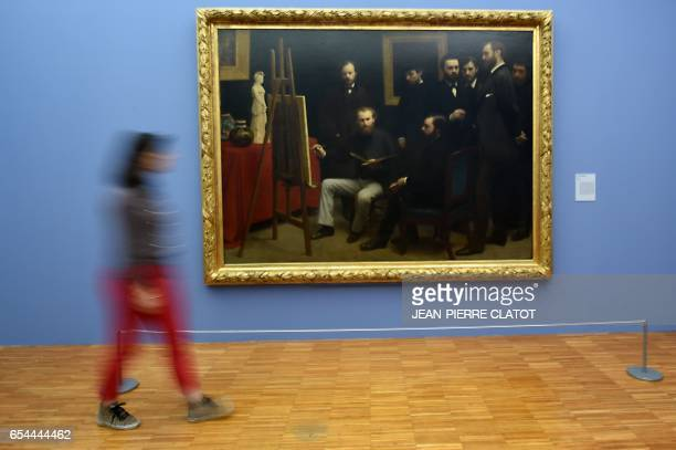 A person walks past a painting titled ' Un atelier aux Batignolles' painted in 1870 by French painter Henri FantinLatour and displayed during the...