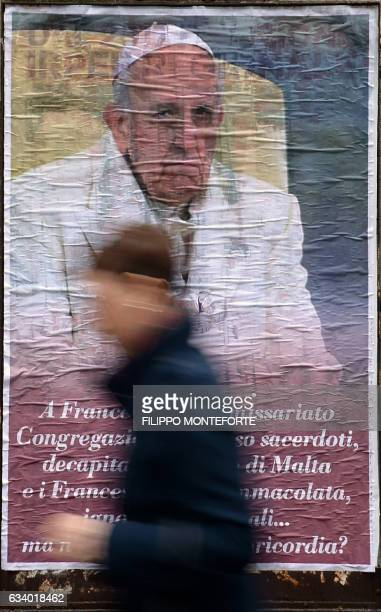 A person walks past an antiPope Francis poster with a portrait of the Pope and a message reading 'Francis you under receivership congregations...