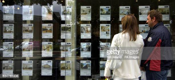 A person walks past an estate agent's window in London after the Chancellor announced that homes worth 175000 or less are to be exempted from stamp...