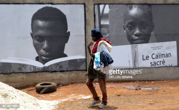 A person walks past posters promoting the 'Conakry 2017 World book capital' event organized by the United Nations Educational Scientific and Cultural...