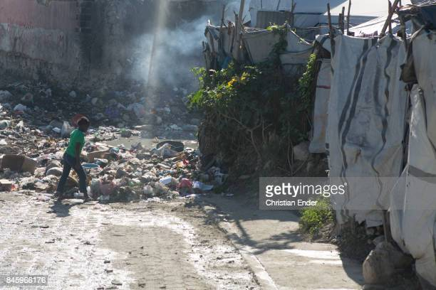 PortauPrince Haiti December 09 2012 A person walks through a street full of trash beside the refugee camp Parc Colofe in PortauPrince The camp exist...