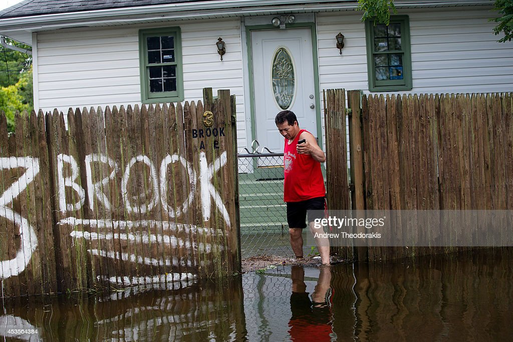 A person walks through flood waters on Brooke Ave following heavy rains and flash flooding on August 13, 2014 in Bayshore, New York. The south shore of Long Island along with the tri-state region saw record setting rain that caused roads to flood entrapping some motorists.