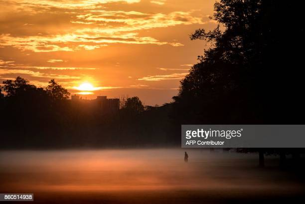 A person walks through morning mist across the Parc de la Tete d'Or in downtown Lyon early on October 12 2017 / AFP PHOTO / JEFF PACHOUD