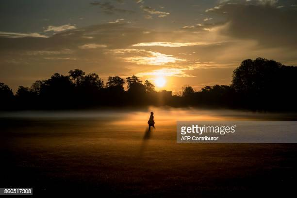 TOPSHOT A person walks through morning mist across the Parc de la Tete d'Or in downtown Lyon early on October 12 2017 / AFP PHOTO / JEFF PACHOUD