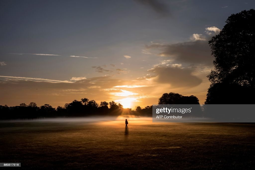 A person walks through morning mist across the Parc de la Tete d'Or in downtown Lyon early on October 12, 2017. /