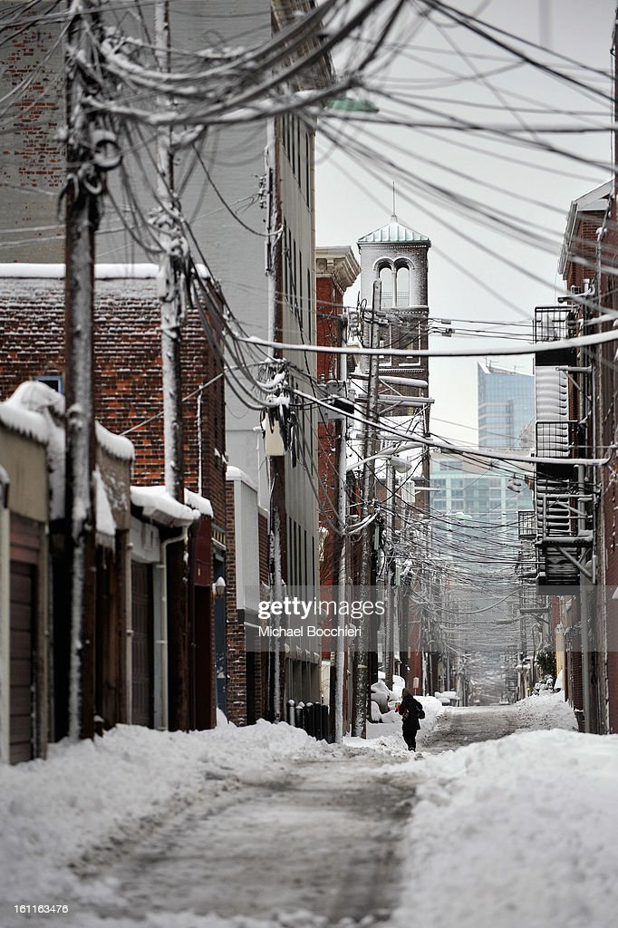A person walks through the snow in an alley following a major winter storm on February 9, 2013 in Hoboken, New Jersey. Much of the Northeast received a foot or more of snow through Saturday morning with possible record-setting blizzard conditions expected. Heavy snow warnings are in effect from New Jersey through southern Maine.