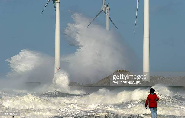 A person watches waves break on a jetty holding wind turbines on November 3 2013 in the Channel port of Boulognesurmer France AFP PHOTO/ PHILIPPE...