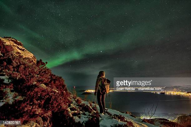 Person watching aurora borealis in sky