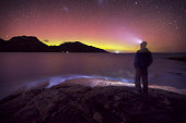 A person watching the aurora australis in the night sky above Coles Bay, Freycinet National Park, Tasmania, Australia