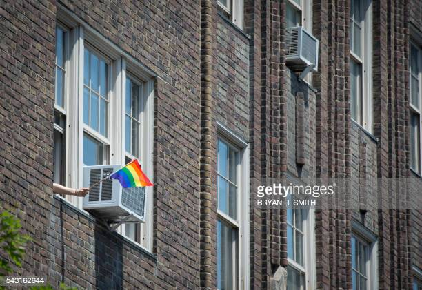 A person waves a flag from window along the parade route during the 46th annual Gay Pride march June 26 2016 in New York New York kicked off June 26...