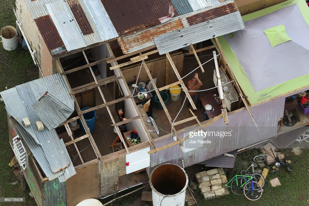 A person waves to a passing helicopter from inside a damaged home as people deal with the aftermath of Hurricane Maria on September 25, 2017 in Toa Baja, Puerto Rico. Maria left widespread damage across Puerto Rico, with virtually the whole island without power or cell service.