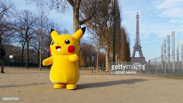 A person wearing a costume of Pikachu a Pokemon character walks on the Champs de Mars near the Eiffel Tower in Paris on December 16 2016 / AFP /...