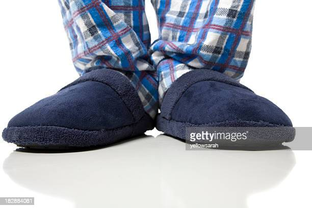 A person wearing a pair of blue slippers with plaid pants