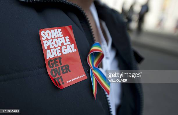 A person wearing a progay sticker looks on as members of the Lesbian Gay Bisexual and Transgender community parade through central London during the...