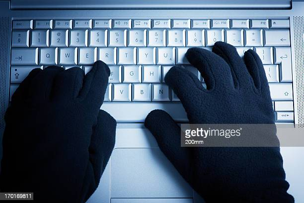 A person wearing gloves while on the computer
