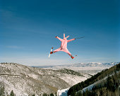 Person wearing pink bunny suit ski jumping, rear view