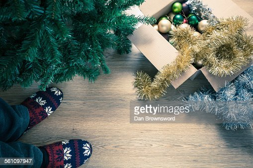 Person wearing slippers with christmas decorations, high angle