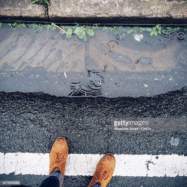 Person Wearing Suede Shoes Standing On White Line Near Roadside Puddle