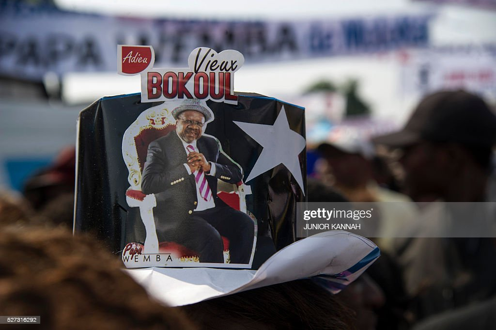 A person wears a hat with a picture of Papa Wemba reading 'Goodbye Vieux Bokoul' (Wemba's nickname) as people gather in the streets of 'Village Molokoi', in the Matonge neighborhood of Kinshasa, to pay tribute to late rumba musician Papa Wemba on May 2, 2016. Democratic Republic of Congo's rumba king Papa Wemba was posthumously awarded one of his country's highest honours, a week after he collapsed on stage and died aged 66. / AFP / JUNIOR