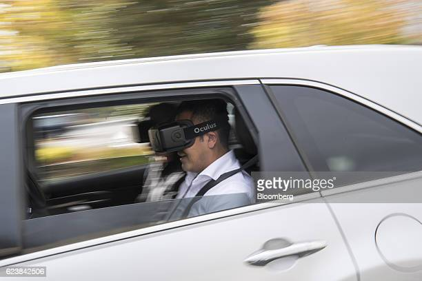 A person wears an Oculus Rift virtual reality headset while riding in a vehicle during a press briefing at the Honda Silicon Valley Lab in Mountain...