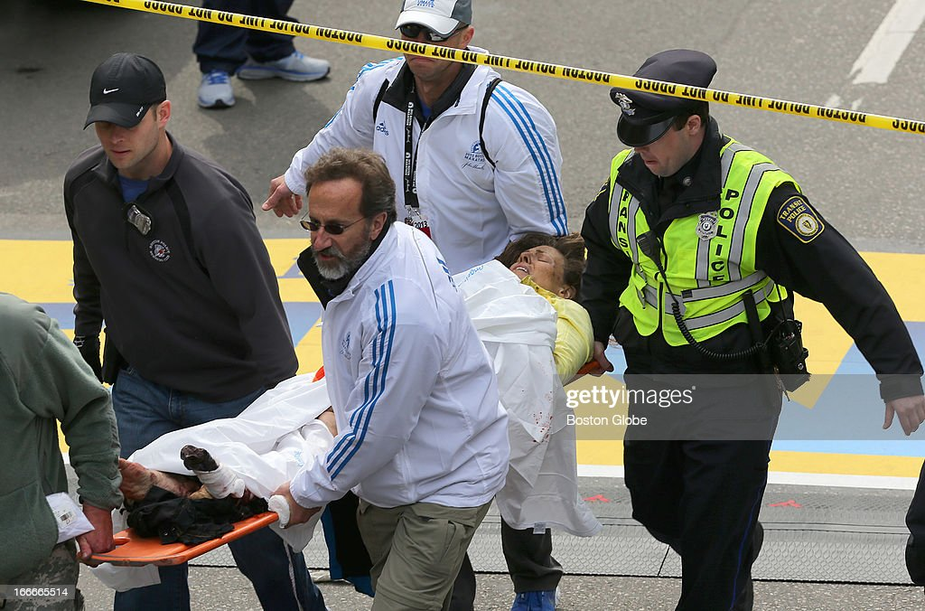A person who was injured in an explosion near the finish line of the 117th Boston Marathon is taken away from the scene on a stretcher.