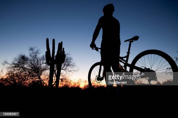 A person with a mountain bike stood at sunset