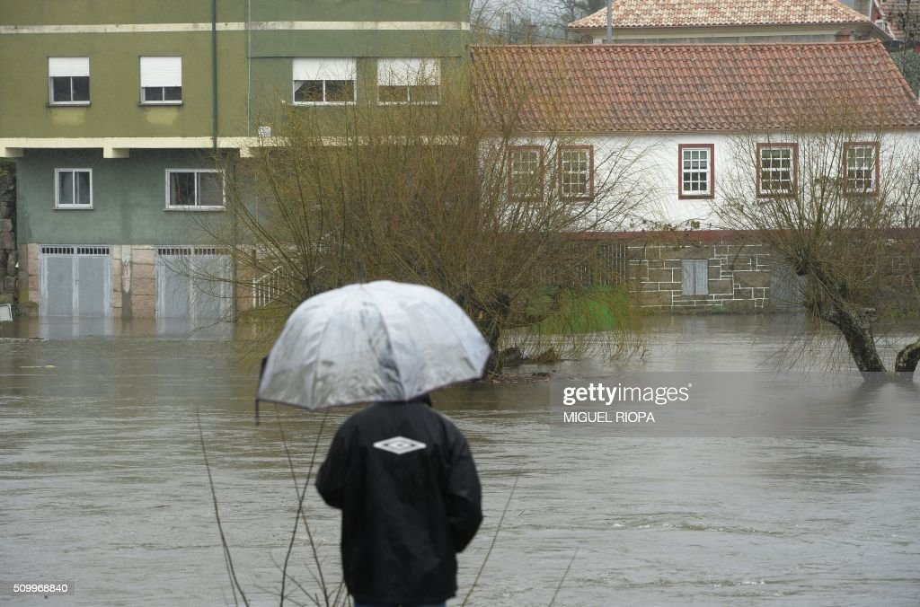 A person with an umbrella looks ast a flooded area next to the river Tea in Ponteareas, northwestern Spain, on February 13, 2016. / AFP / AFP or licensors / MIGUEL RIOPA