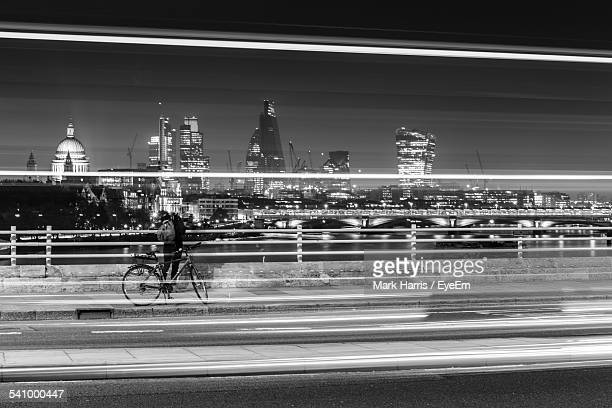 Person With Bicycle Standing On Waterloo Bridge At Night