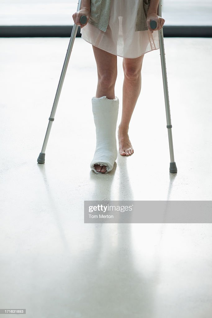 Person with cast on leg using crutches