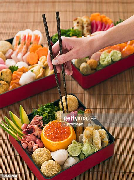Person with chopsticks and Japanese New Year bento box