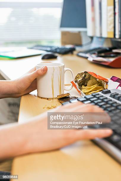 person with dripping mug and treats on office desk