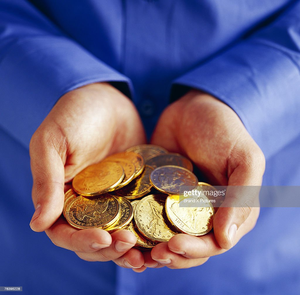 Person with handful of gold coins : Stock Photo