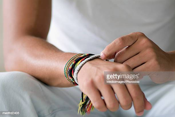 Person with rope bracelets on wrist, close-up, midsection
