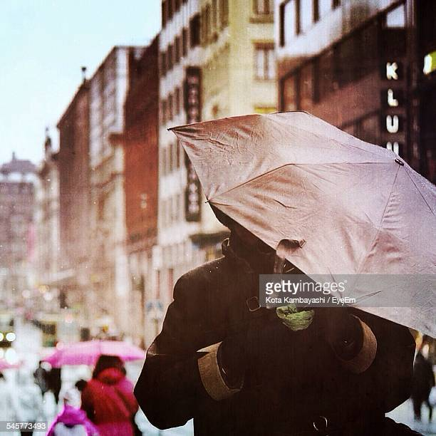 Person With Umbrella Standing In City