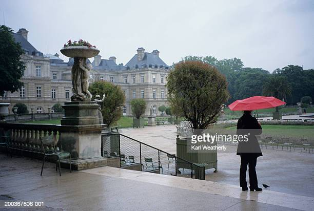 Person with umbrella standing in Luxembourg Park, Paris, France