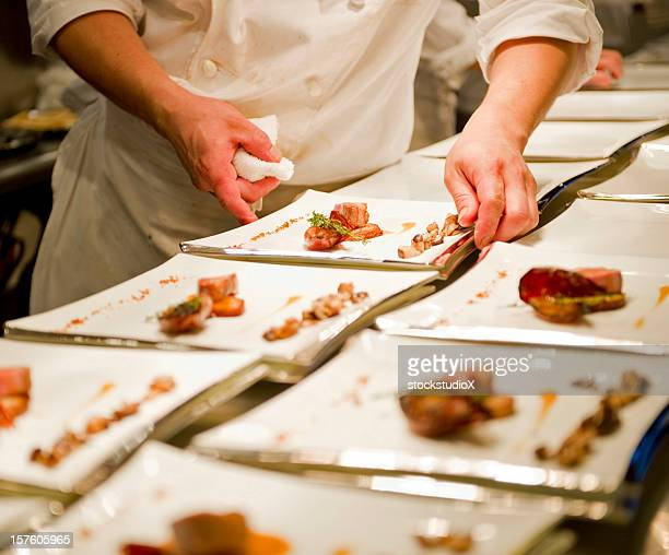 A person working in a kitchen and plating food