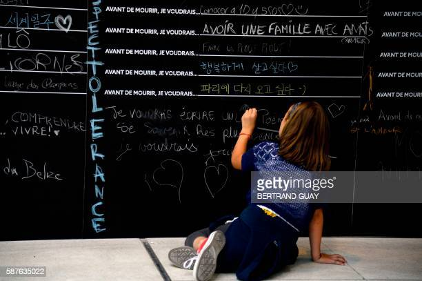 A person writes a notes on the collaborative art installation 'Before I die' by US artist Candy Chang on August 9 2016 at the Gare de Lyon in Paris...