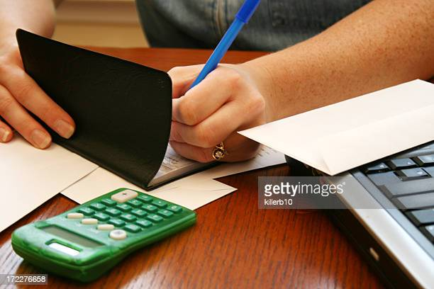 Person writing in a black book next to calculator and laptop
