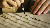Close up of person carefully writing traditional Japanese calligraphy with a fudepen.
