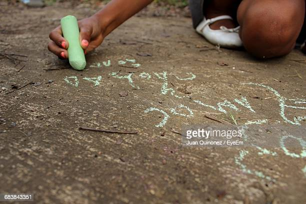 Person Writing On Ground With Chalk