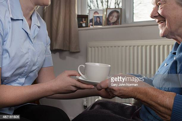 Personal care assistant handing senior woman cup of tea