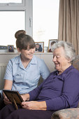 Personal care assistant looking at photograph with senior woman