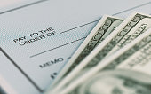 Close-up picture of a personal check and American Dollars with selective focus. Great use for financial concepts.
