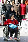A personal nurse pushes a wheel chair of an elderly woman along a street in Beijing 25 October 2005 China needs at least 22 million nurses to care...