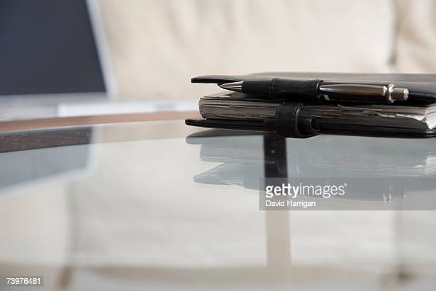 Personal organizer on a glass coffee table in front of a laptop on a sofa