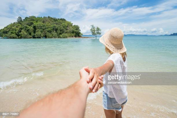 Personal perspective of man holding young woman by hand on the beach